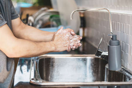 Closeup-up Asian man hand washing with faucet water in kitchen at home, Health care pandemic , cleaning and carefree concept