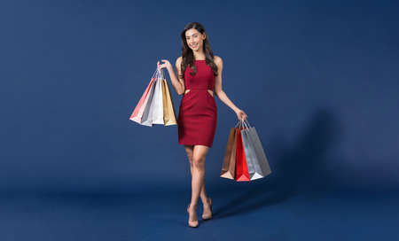 Happy young Asian woman wearing red dress carrying multi color shopping bags on blue color background, exciting for sales discount, black friday and consumerism concept, summer fashion, Full body. Zdjęcie Seryjne