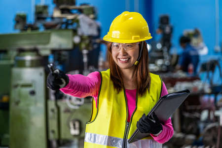 Portrait of Asian woman sales engineer checking the job list in paper over the photo blurred of lathe and milling machine background in metal factory, business industry with safety concept Zdjęcie Seryjne