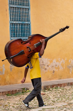 man carring a bass on a street of Trinidad, Cuba Stock Photo