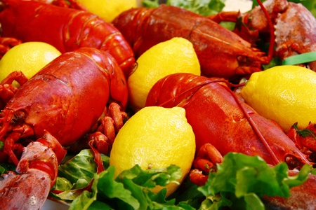 sea food made of lobsters, lemons and green salad