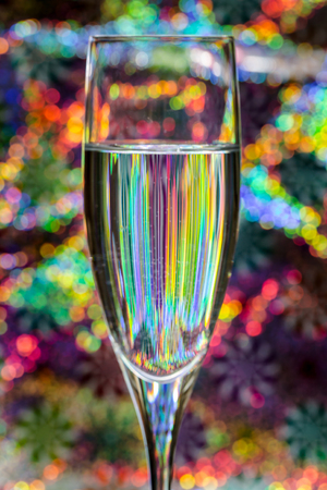 Still image of a glass of wine against colorful background creating intriguing reflections