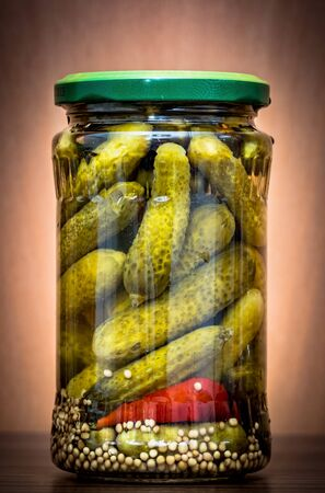 Jar of pickled cucumbers against wooden background