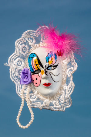 Carnival mask with feathers and beads against blue sky