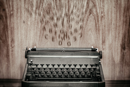 Vintage typewriter with letters flying against wooden background,suggesting inspiration Stock Photo