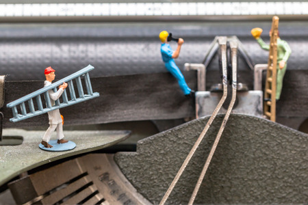 Team of miniature workers performing maintenance activities Stock Photo