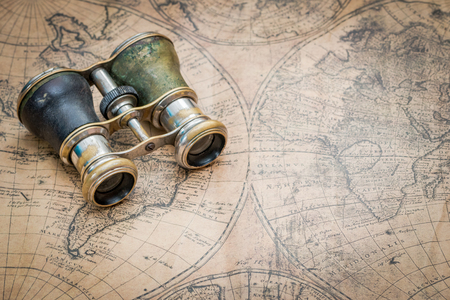 Travel concept with binoculars set on a vintage map