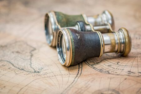 Old binoculars on an antique map Stock Photo
