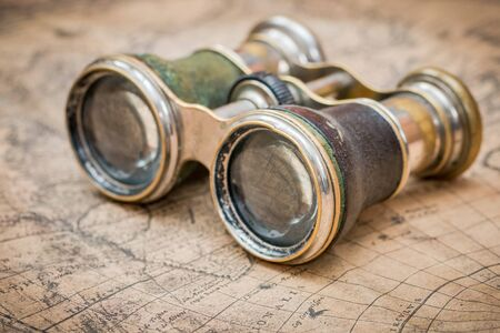 Binoculars set on an antique map