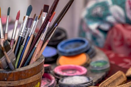 Brushes in a container on a painters desk Stock Photo