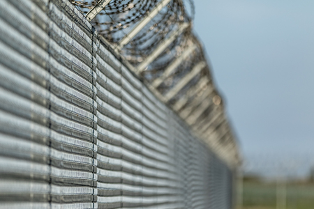 Barbwire fence against illegal immigration Stock Photo