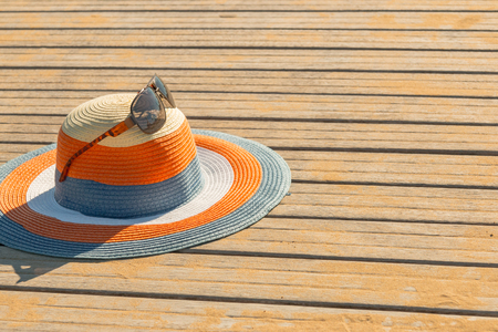 Colorful straw hat with sunglasses, set on a wooden floor