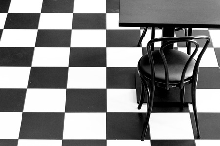Black and white chess floor with black chiar and table
