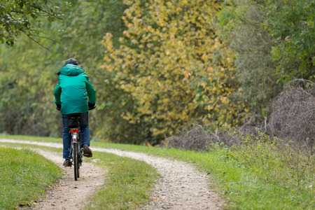 Man riding a bike on a forest road Stock Photo