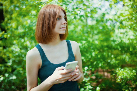 lady on phone: Young woman making photo on cellphone, spring flowers background Stock Photo