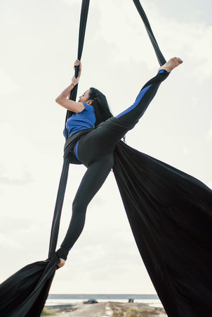 Elegance young beautiful woman dancing with aerial silk on a sky background. Fly yoga sport Stock Photo