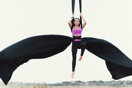 Elegance young beautiful woman dancing with aerial silk on a sky background. Fly yoga sport Reklamní fotografie