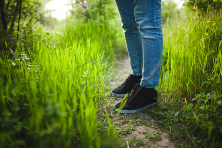 The man is standing in the grass. Vibrant background of lush blades of green grass