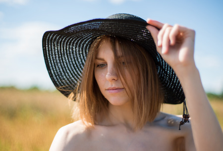 Portrait of a young beautiful woman in a hat on the field Stock Photo