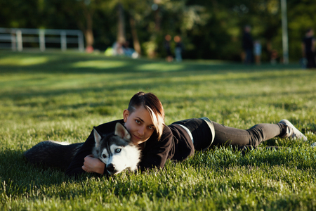 Beautiful young woman playing with funny husky dog ??outdoors in park at sunset or sunrise
