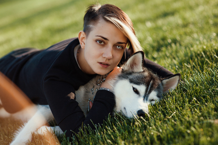 fidelidad: Beautiful young woman playing with funny husky dog ??outdoors in park at sunset or sunrise