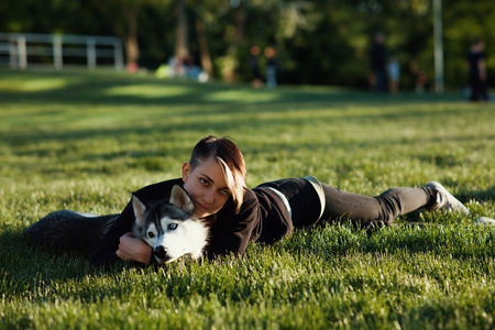 winter sunrise: Beautiful young woman playing with funny husky dog ??outdoors in park at sunset or sunrise