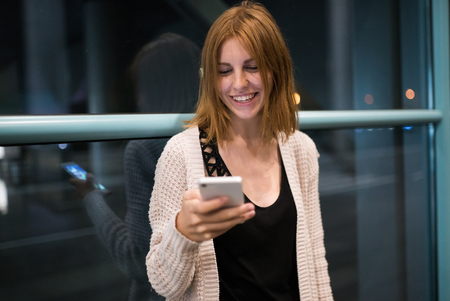 beautiful young red-haired woman using smartphone or cell phone at night on street