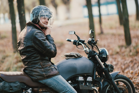 Motorcyclist on the old cafe-racer motorcycle, autumn background Standard-Bild