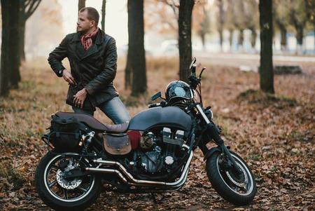 Motociclista en la vieja motocicleta café-corredor, fondo de otoño