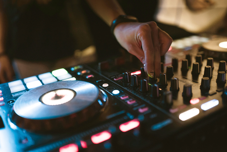 Hands of woman DJ tweak various track controls on djs deck at night club Stock Photo