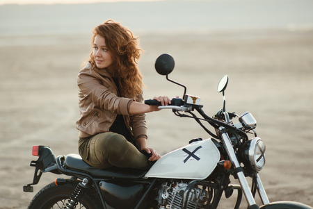 young beautiful woman sitting on her old cafe racer motorcycle in the desert at sunset or sunrise