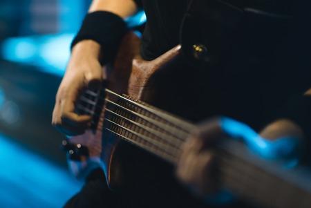 コンサートステージでエレクトリックギターを演奏するマンベースギタリスト 写真素材