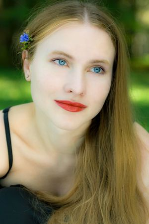 Pretty smiling blond woman with blue eyes posing with a small blue flower Stock Photo - 5654237