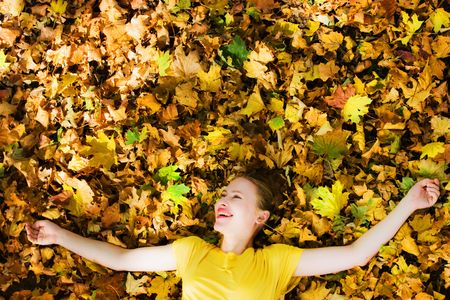 beautiful young blond woman on yellow autumn leaves photo