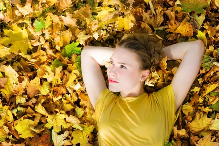 beautiful young blond woman on yellow autumn leaves Stock Photo