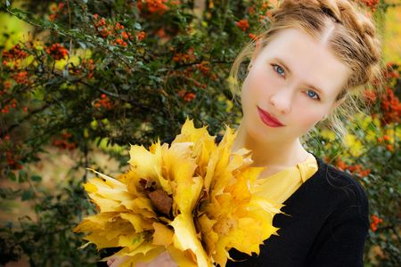 beautiful young blond woman with yellow autumn leaves photo