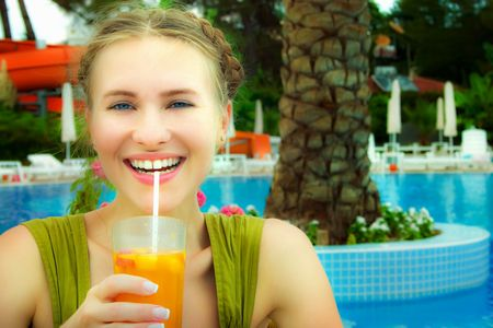 Young blond beautiful woman near the swiming pool at mediterranean resort drinking orange cocktail photo