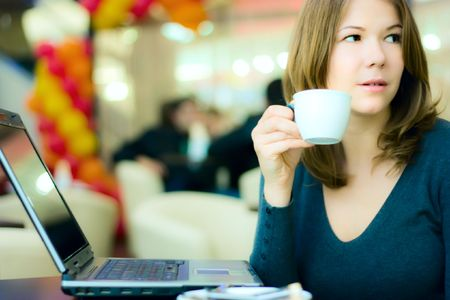 young pretty business woman drinking coffee in cafe and working on laptop Stock Photo - 5867901