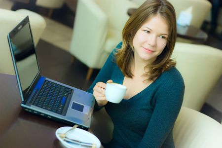 young pretty business woman drinking coffee in cafe and working on laptop Stock Photo - 5867902