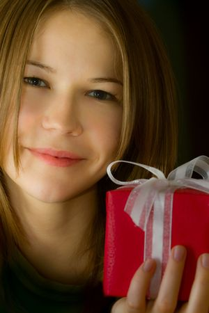 portrait of young beautiful smiling woman with a small red gift box photo