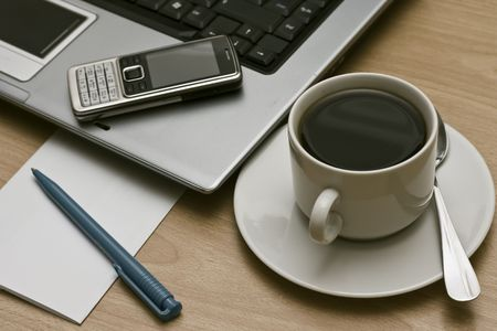 business communications - laptop, cell mobile phone  and cup of coffee on a desktop