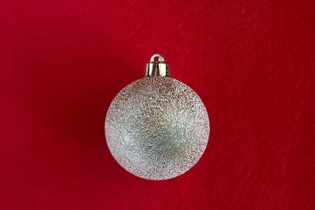 Christmas bauble on dark red background - see more photo