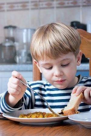 little beautiful boy eating at the kitchen photo