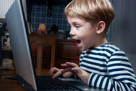learning computer: bambino giocando il gioco per computer molto emotivo Archivio Fotografico