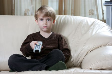 cute little boy sitting on the sofa and watching tv with a remote control photo