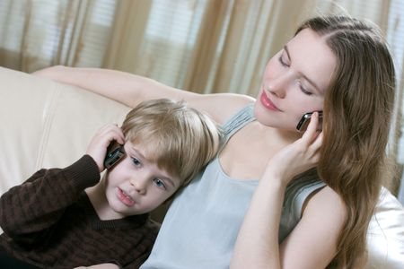 family phone talking - cute little boy and his mother are sitting on the sofa and talking by cell phone photo
