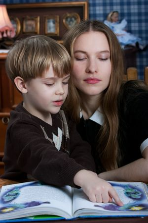 beautiful young mother with her little son reading the book at the table Stock Photo