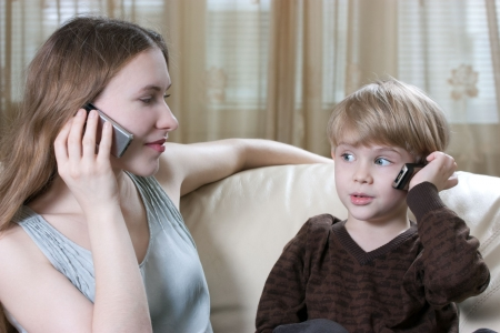 family phone talking - cute little boy and his mother are sitting on the sofa and talking by cell phone Stock Photo