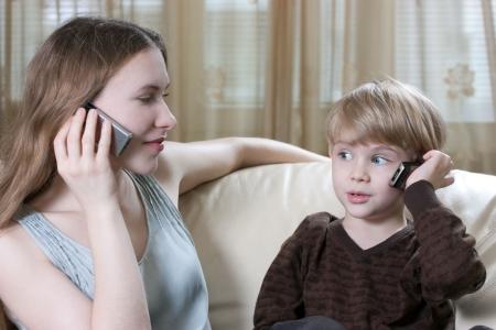 ni�os hablando: hablando de tel�fono familiar - lindo ni�o peque�o y su madre son sentado en el sof� y hablando por tel�fono celular
