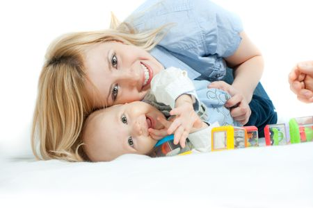 Happy family: mother and baby lying on the bed, playing and smiling Stock Photo